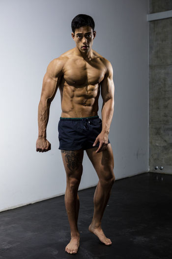 Full body shot of a musical fitness model standing behind a white wall. Adult Asian  Athlete Body & Fitness Human Body Looking At Camera Man Nam Vo Shirtless Sportsman Clenched Fist Fitness Model Full Body Shot Grey Wall Handsome Hunk Male Muscle Muscular Build One Person Strong Studio Shot Tatoo Thighs Torso