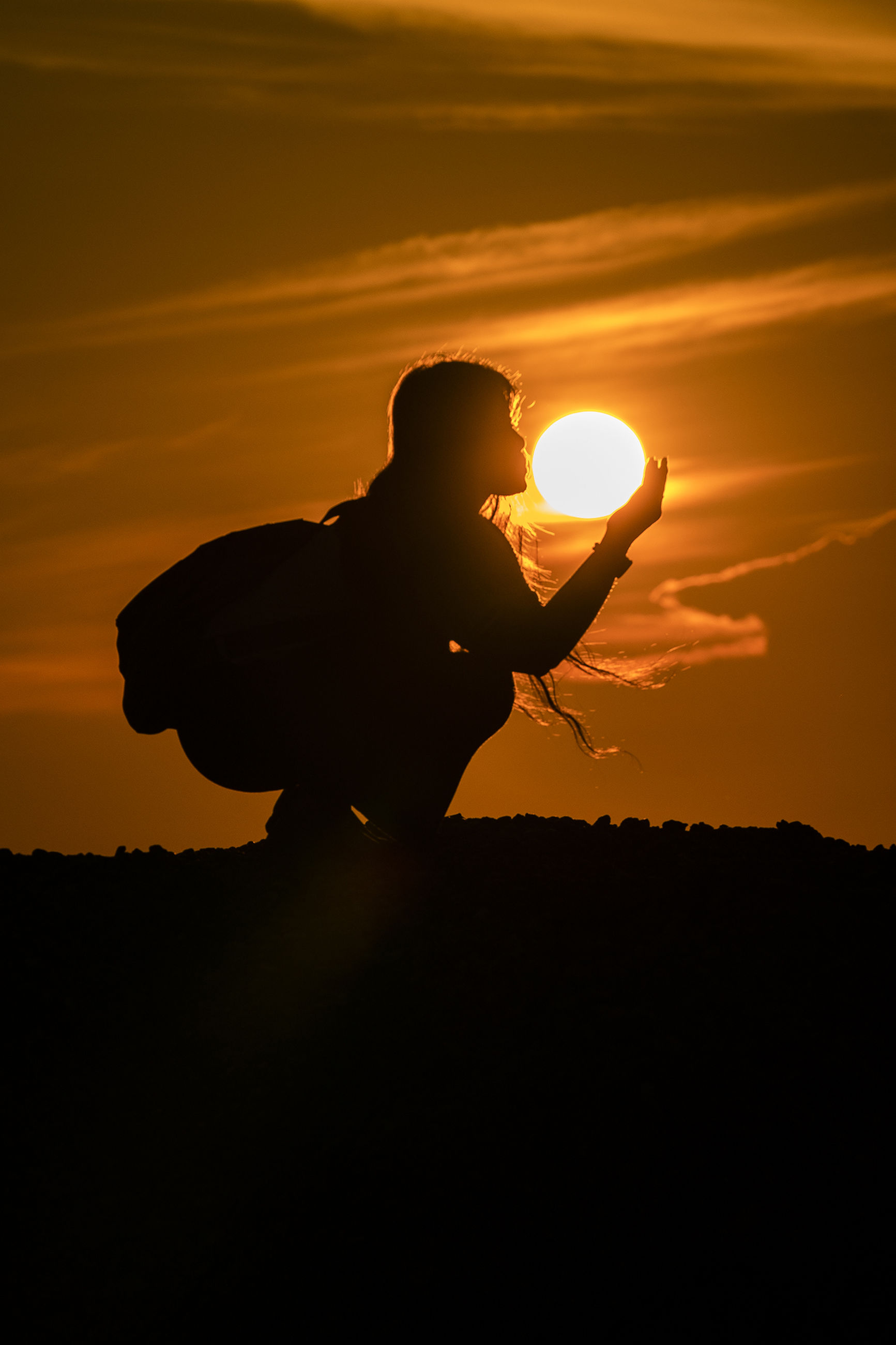 sunset, sky, orange color, silhouette, one person, beauty in nature, real people, lifestyles, men, sun, nature, scenics - nature, leisure activity, holding, cloud - sky, standing, tranquility, outdoors, land