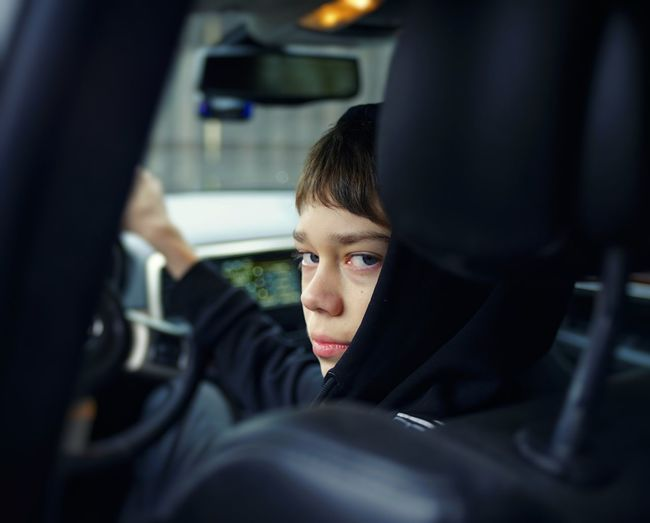 Portrait of teenage boy driving car