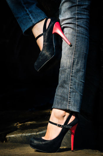 Low section of woman wearing stilettoes standing on floor