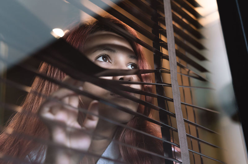 Close-up of woman looking away through blinds and window
