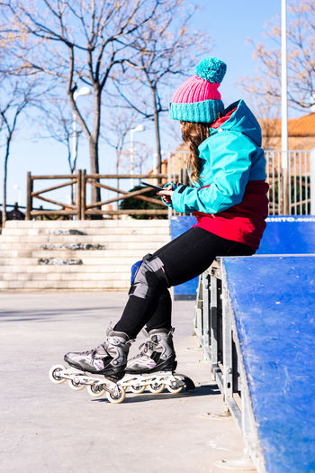 Full length side view of woman wearing inline skates outdoors
