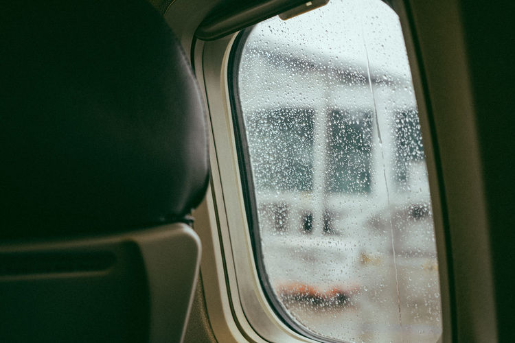 Close-Up Of Vehicle Seat By Wet Window In Airplane