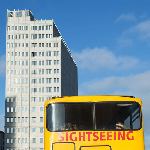 Low Angle View Of Yellow Bus By Building Against Sky