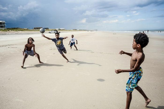 FULL LENGTH OF FRIENDS ENJOYING ON BEACH