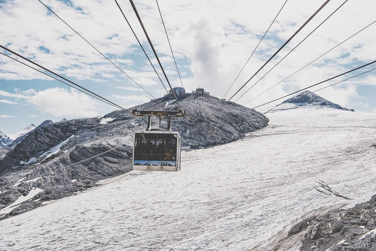 Cable car over snow covered land against sky