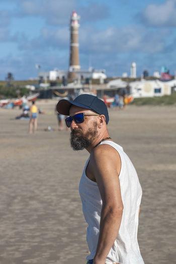 Man wearing sunglasses standing on beach