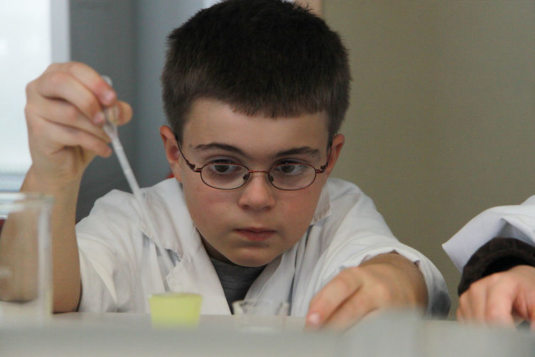 Young boy wearing glasses wearing lab coat making experiments in the lab Childhood Concentration Day Experimant Experimental Generation Glass - Material Headshot Indoors  Lab Lab Work Learn & Shoot: After Dark Medicine Medicines Milennial One Person People Pink Color Quiet Moments Research Research And Development School Teacher University