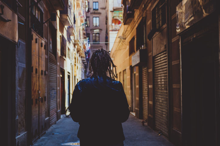 Rear view of man with dreadlocks standing amidst buildings on alley in city
