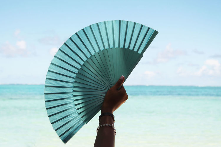Woman holding fan by sea against sky