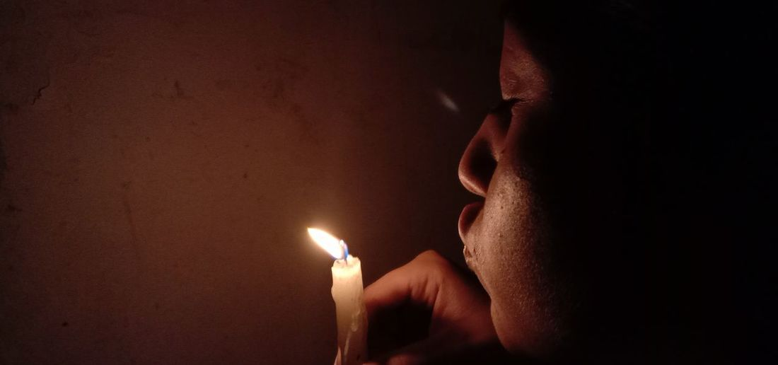 Close-up of woman blowing candle