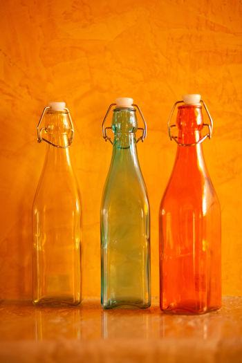 Empty bottles on table against orange wall