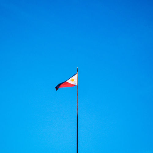 Low angle view of flag flags against clear blue sky