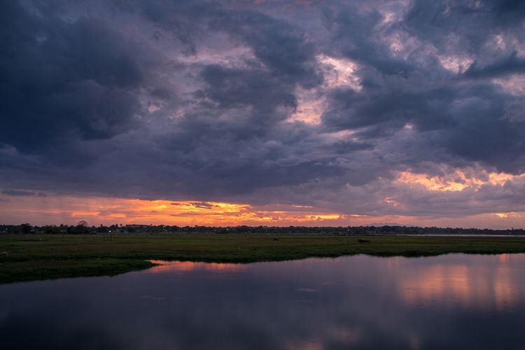 Scenic view of dramatic sky over lake during sunset