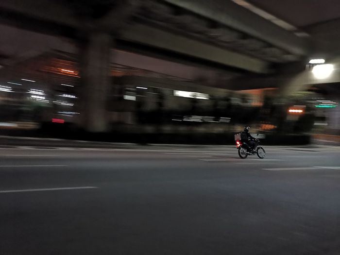 Blurred Motion Motion Motion Blur City Biker Motorcycle Full Length Road Headwear Land Vehicle Riding Bicycle Cycling Traffic Tail Light Moving Vehicle Light Racing Bicycle Road Sign Vehicle High Street Multiple Lane Highway Light Trail Highway Elevated Road Stoplight