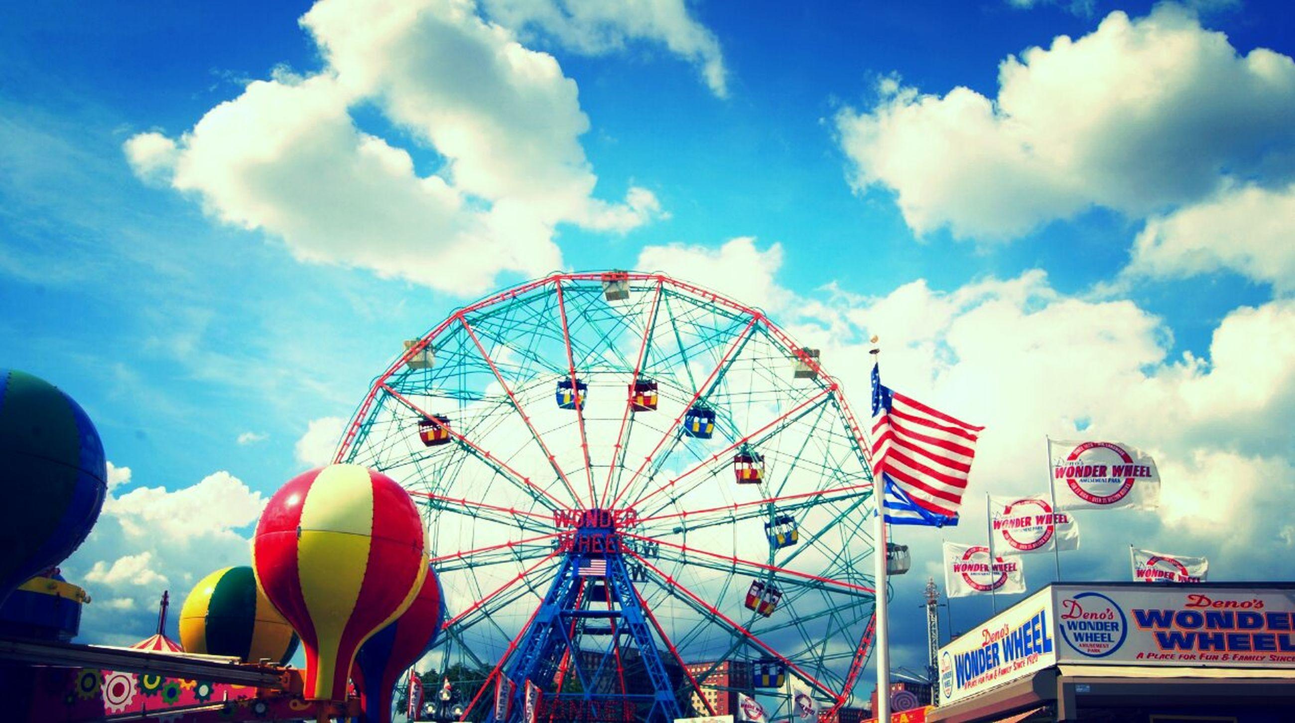 sky, amusement park, amusement park ride, ferris wheel, cloud - sky, arts culture and entertainment, low angle view, multi colored, built structure, cloud, cloudy, blue, architecture, fun, outdoors, day, leisure activity, no people, enjoyment, travel