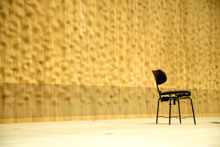 Empty chairs against curtain