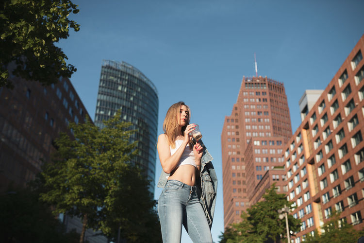 Low angle view of woman drinking coffee against buildings