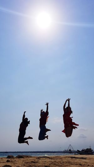 Silhouette friends jumping at beach air against sky during sunny day