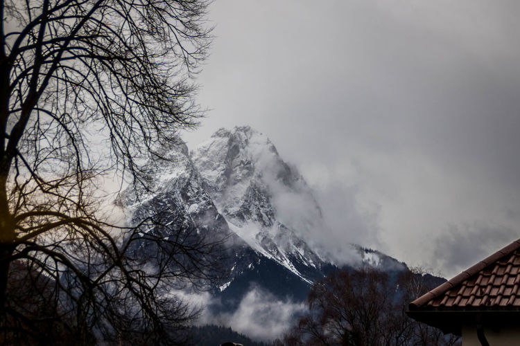 Tree Sky Mountain Beauty In Nature No People Plant Winter Nature Cloud - Sky Cold Temperature Scenics - Nature Building Exterior Snow Architecture Day Low Angle View Fog Built Structure Roof Outdoors Snowcapped Mountain Snowing