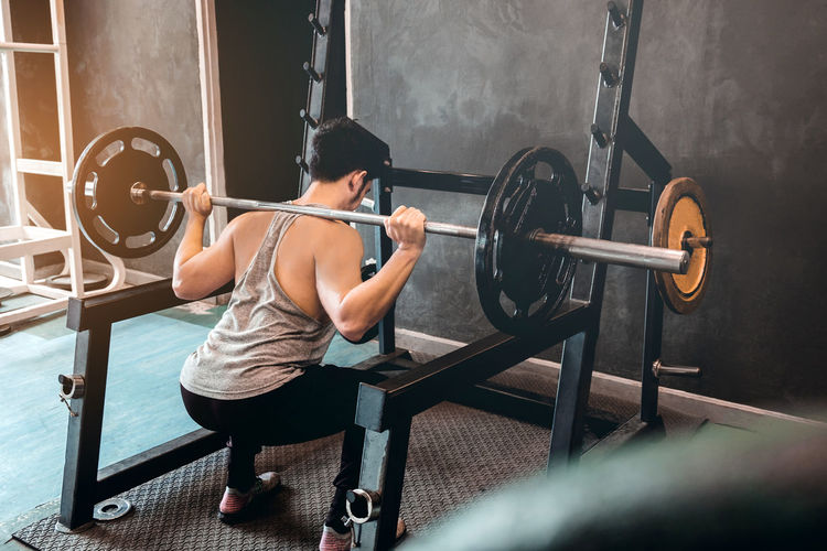 Rear view of man exercising with barbell at gym