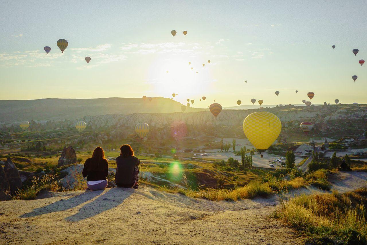 Women looking at hot air balloons while sitting on mountain at cappadocia