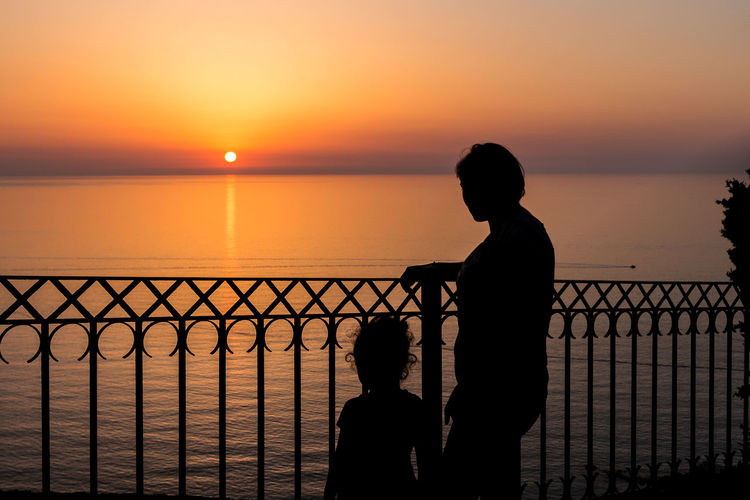 Silhouette of mother and daughter standing by railing against sea during sunset