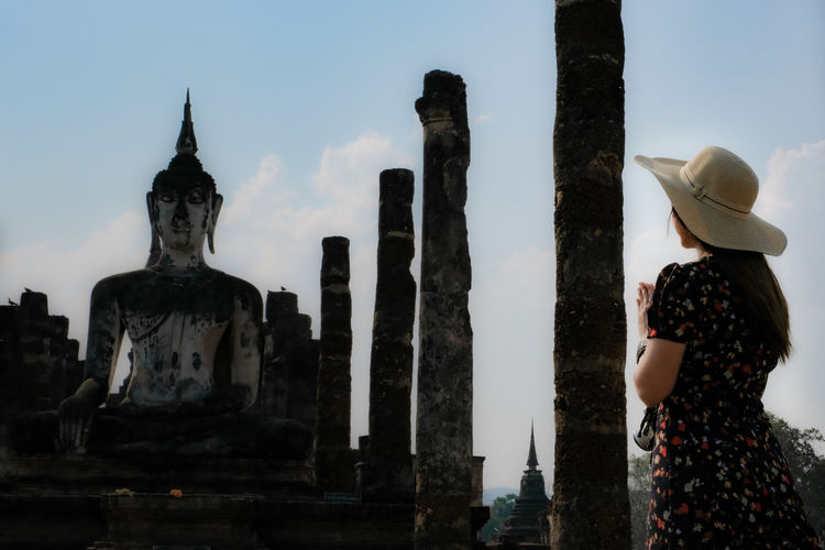 Rear view of woman in front of old buddha statue against sky