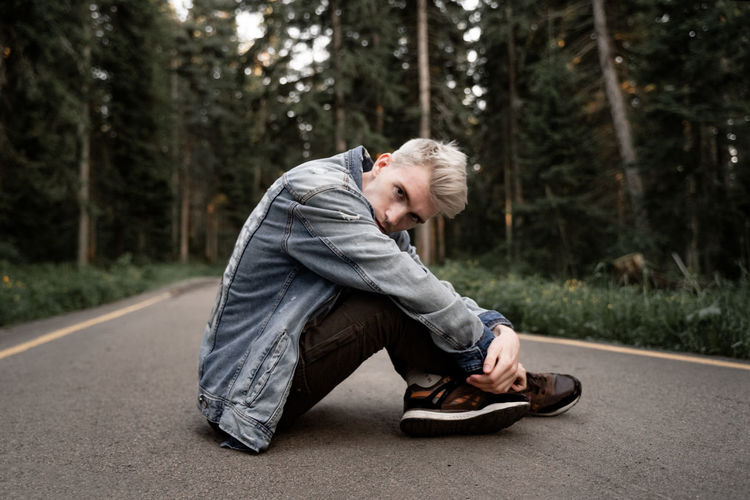 Side view portrait of man sitting on road in forest