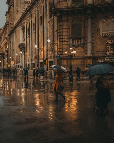 People walking on wet street during rainy season