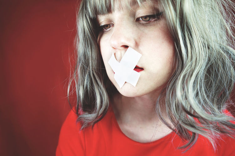 Close-up of sad woman with tape on her mouth