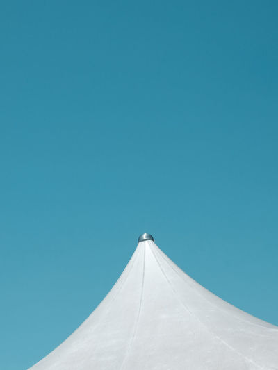 Low angle view of white fabric roof against clear blue sky