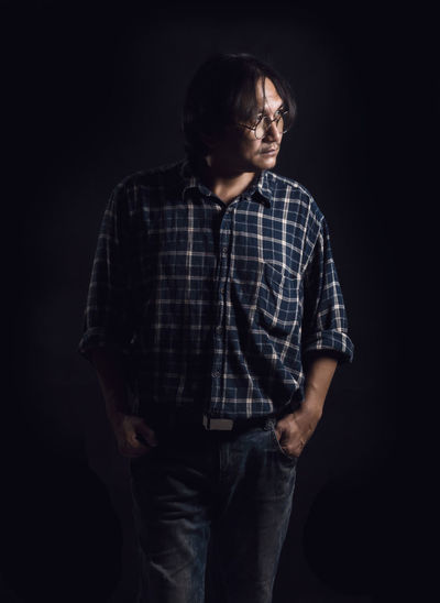 Middle aged man On a black background The concept of working people. Jeans Studio Shot Indoors  Black Background One Person Standing Casual Clothing Three Quarter Length Checked Pattern Young Men Young Adult Lifestyles Men Front View Real People Looking Emotion Contemplation Adult Sadness Plaid Shirt  Teenager Depression - Sadness Obscured Face Hairstyle