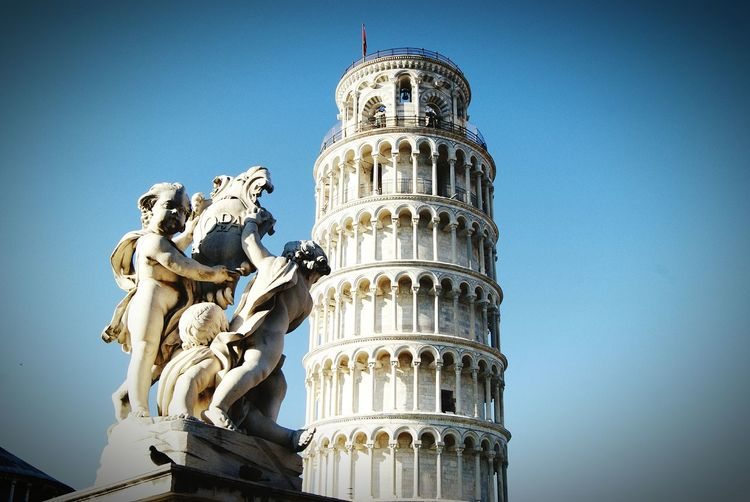 Statue by leaning tower of pisa against clear blue sky