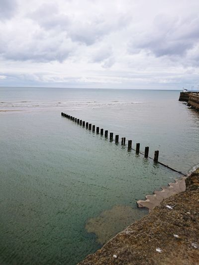 Wooden Posts Pier Cloudy Day Sea Water Beach Sky Horizon Over Water Cloud - Sky