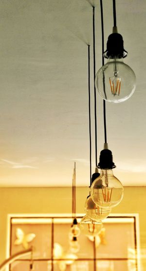 Low angle view of light bulbs hanging from ceiling at home