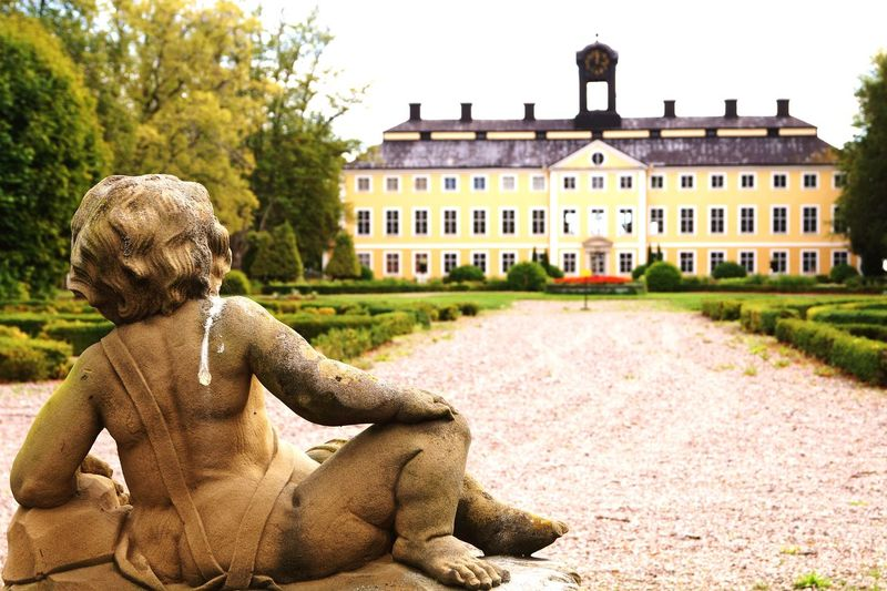 Guardian by The castle Birdshit Statue Sturefors Castle EyeEm Selects Architecture Building Exterior History Statue Travel Destinations Outdoors Tree Day Nature Sky Royal Person Sculpture Rear View Built Structure Grass