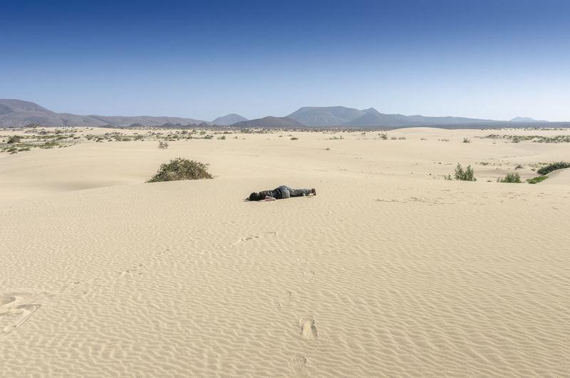 Woman fainted in desert sand. Canary Islands Destruction Drain Drought Fuerteventura Tourist Woman Arid Climate Barren Clay Climate Dirt Dry Dune Faint Infertile Mud Nature Outdoors Problem Sand Sand Dune Surface Testure Thirsttrap