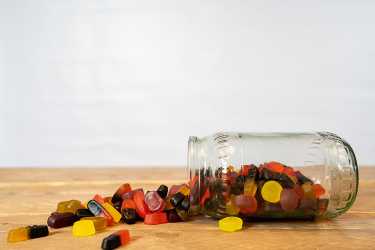 candy jar on his side. Candy out of the jar on the wooden table. white background Large Group Of Objects Still Life Table Container Indoors  Glass - Material Choice Wood - Material Food And Drink Abundance Variation Jar Bottle No People Close-up Candy Candies Colored Jellyfish Treats Temptation Delicious Tasty Sweet Food Sweets Wooden Wooden Table White Background Backgrounds Copy Space Eating Food Child Childhood Multicolored Side View Sugar Birthday Card Fresh Full Group Nobody Yellow Black Red Orange