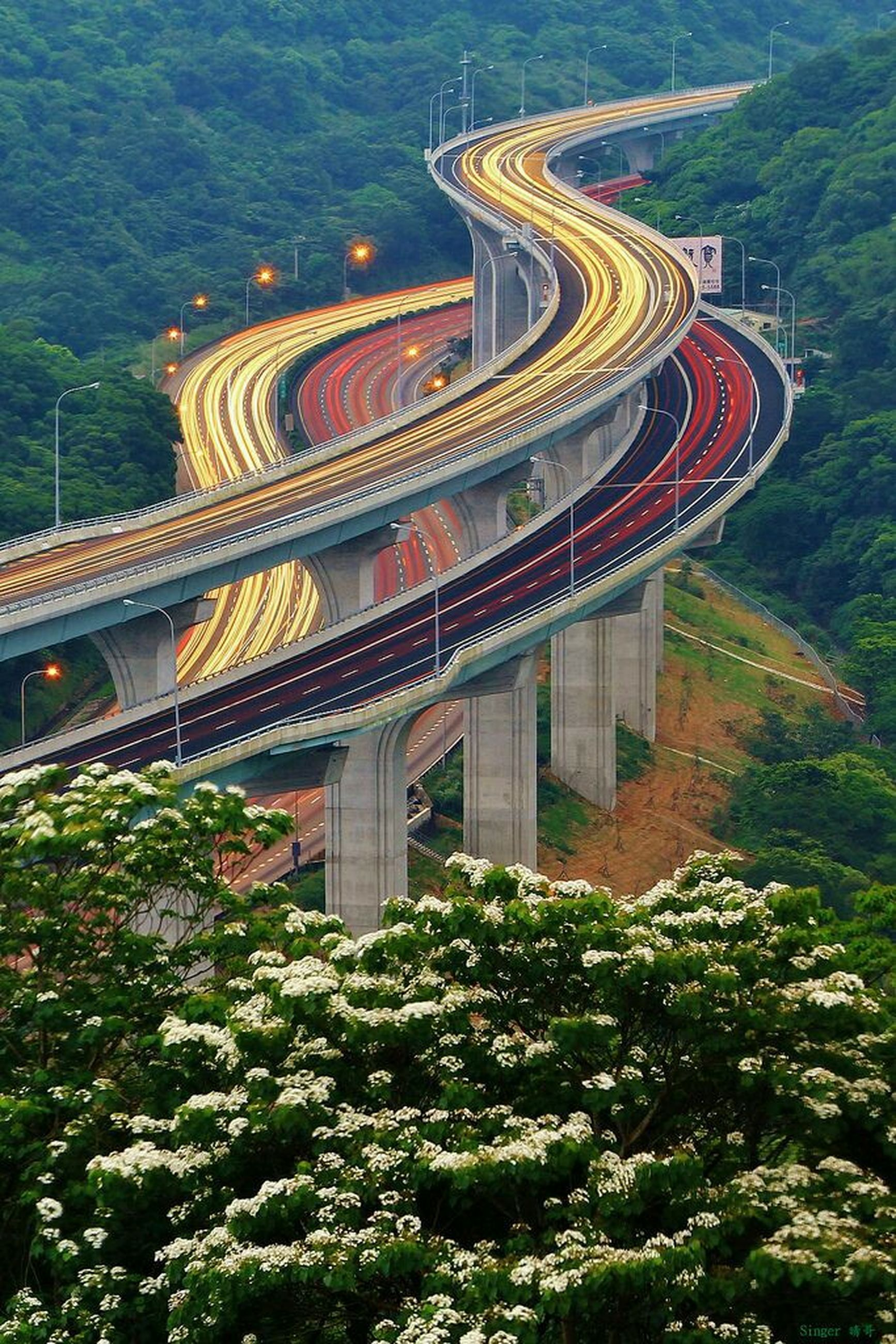 architecture, built structure, tree, connection, high angle view, transportation, bridge - man made structure, building exterior, travel destinations, growth, travel, landscape, green color, outdoors, road, mountain, curve, forest, tourism, city