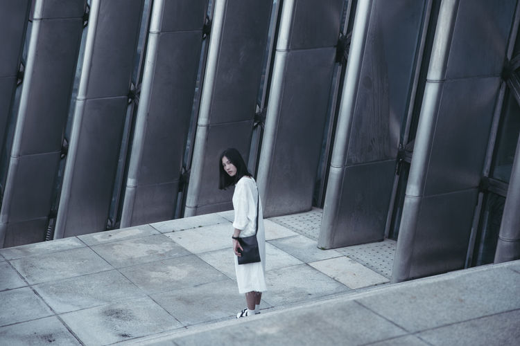Portrait of young woman standing by modern building