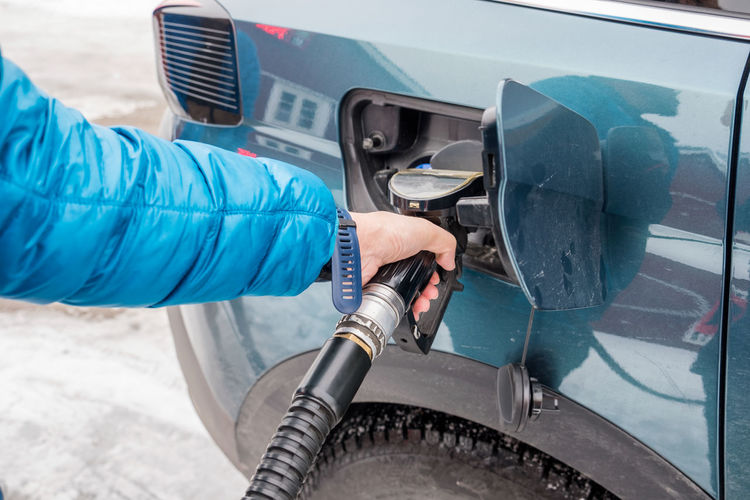 Cropped hand refilling car with fuel