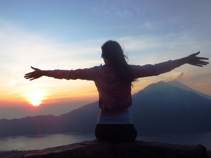 Rear View Of Woman With Arms Outstretched While Sitting On Rock Against Sky During Sunset