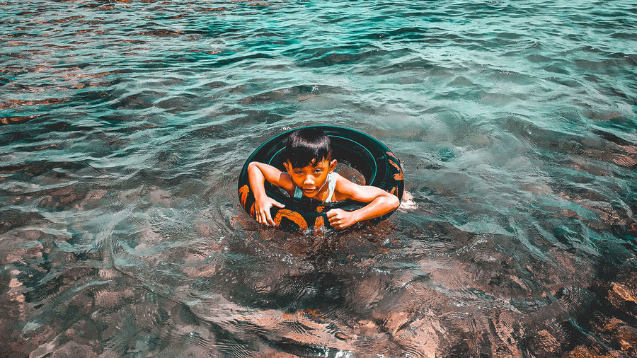 High angle view of man sitting in sea