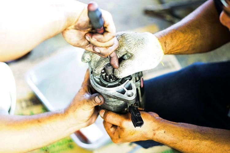 Cropped Hands Of Repairmen Holding Equipment