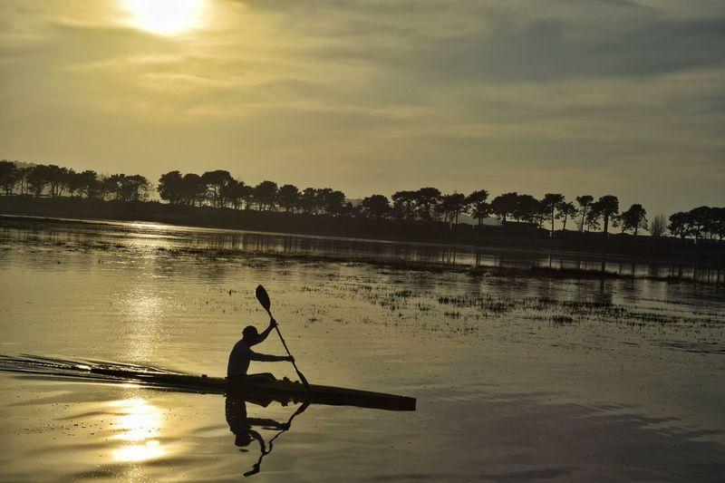 Man kayaking at lake against sky during sunset