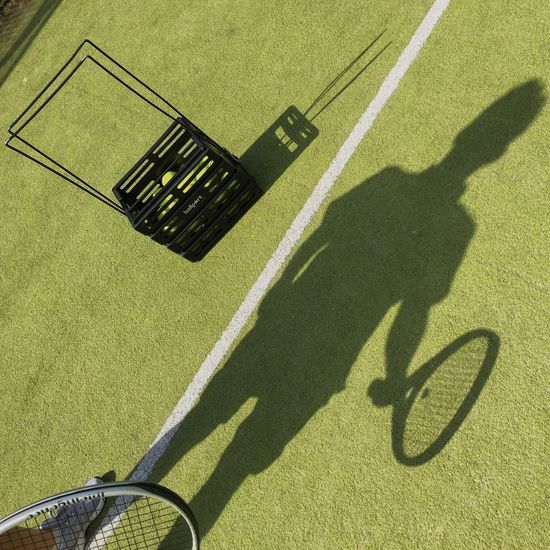 Shadow Of Tennis Player With Racket On Court During Sunny Day