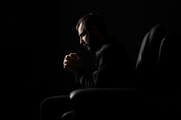 Worried man sitting on armchair in darkroom