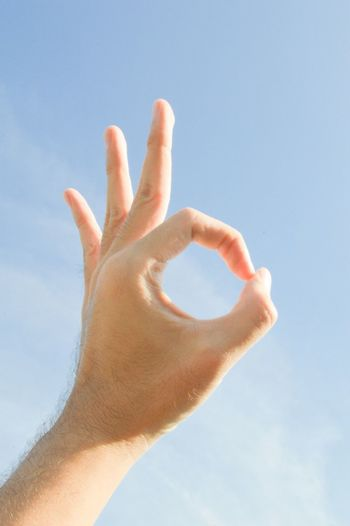 Cropped hand showing ok sign against sky