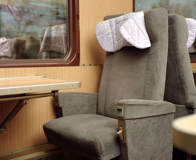 Seat and table by window in train